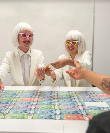 Two people dressed all in white on the far side of a table which has Canadian bills on it. One person on the close side of the table reaching out to the people dressed in white.
