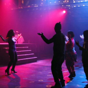 A group of people dancing with Carmen Aguirre facing, leading them. In a darkened room.