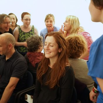 Close up of a group of people, some seated with their eyes closed, some close to them speaking.