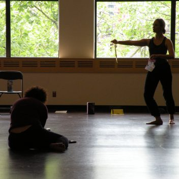 Joanna Garfinkel & Natalie Schneck in rehearsal. One standing with their hand out, the other sitting on the floor