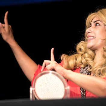 Close up of Anita Majumdar with a blonde wig. Both hands on the left, in the air with one finger of each hand pointed up.