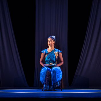 Anita Majumdar sitting on a chair, looking slightly to the side in a blue outfit with a blue stage
