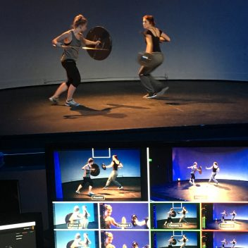 Alice Cavanagh & Siobhan Richardson rehearsing with swords and shields. There are a few monitors, which are showing various angles of them.