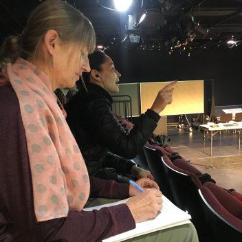 Patti Flather, and Reneltta Arluk sitting on theatre seating, making notes.