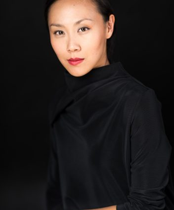 Jasmine Chen, seated looking straight ahead, wearing black with a black background