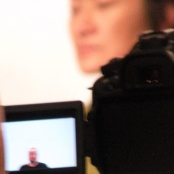 Close up of a camera, with the head of the operator. Someone is in front of the camera, that person is on the screen of the camera.