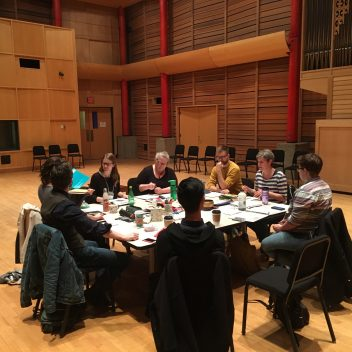 Group of people sitting around a table in a rehearsal hall.
