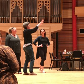 Three people in rehearsal, one is pointing up at something. The other two are looking at that person. The walls are wooden and there is a table and some chairs