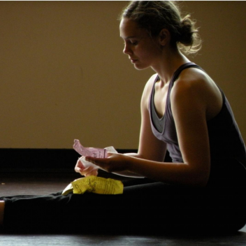 Two images next to each other of Natalie Schneck. One, seated with their legs out in front of them, the other they are laying on their back with one leg up.
