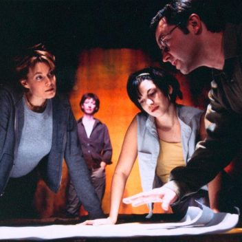 Four people in the foreground around a table looking at a large sheet of paper. One person in the background, watching them.