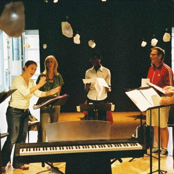 Seven people rehearsing, with a keyboard in the foreground