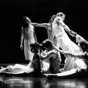 A group of people in movement. Some are seated on the floor, others are standing. They are all connected, by their arms. It's in black and white.