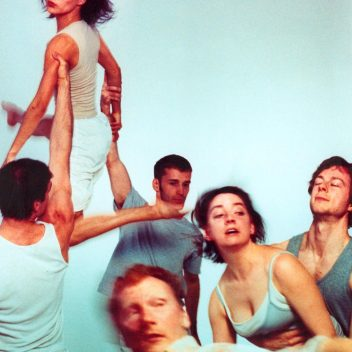 A group of people, all wearing light grey and white. They are all in movement, one is being lifted by their arms by two others.