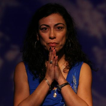 Close up of Carmen Aguirre with their hands in front of their chin, pressed together.
