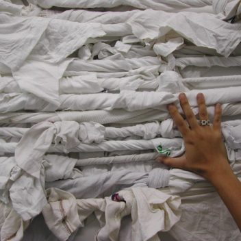 A hand in front of white fabric that has been twisted into rope