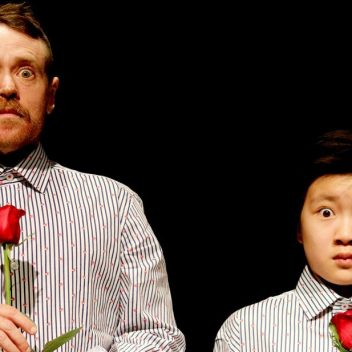 Sunny Drake and Eponine Lee wearing matching shirts, standing next to each other, eyes wide and holding a rose