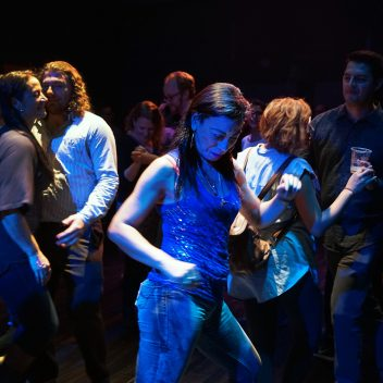Carmen Aguirre dancing, with audience members behind her, also dancing