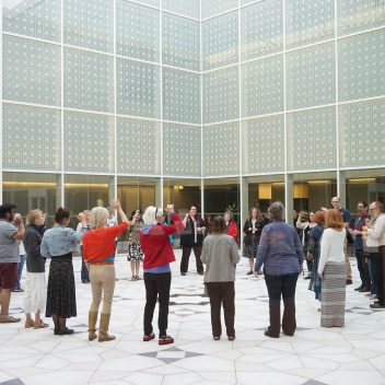 A circle of people, some with their hand raised. They are standing in a courtyard.