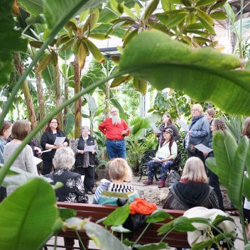 A group of people in a circle, some of them are holding papers in front of them. They are in an indoor garden space.