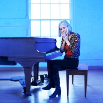 Jane Miller sitting in front of a piano, with their palms together in front of their face