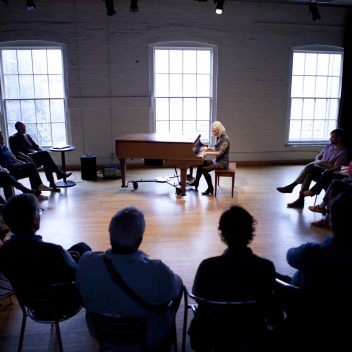 Jane Miller seated, playing a piano. A circle of people are seated around the piano, listening. The circle of people are in darkness and Jane is lit up.