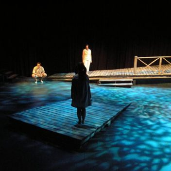Three people on stage, with blue light on the floor. One is sitting on their heels, facing the front. One is standing on a wooden dock facing forward. The other is standing on a different wooden dock, with their back to the front.