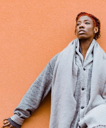 Myekah Payne in front of an orange wall, they are wearing grey