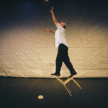 Andy Massingham standing and balancing on a tipping chair, reaching up