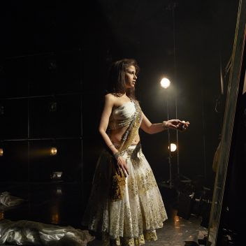 Anita Majumdar backstage with their left hand outstretched