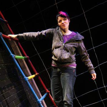 Michaela Washburn hanging sideways off a colourful ladder
