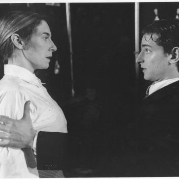 Close up of Tracey Ferenz and Jordan Pettle facing each other. Jordan has their hand on Tracey's arms. Black and white image