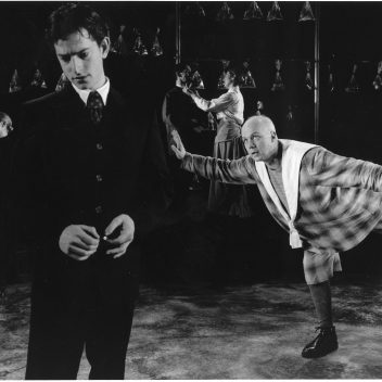 Three people in the background. Two people in the foreground, one is leaning forward on one leg with their arms outstretched, one is looking down