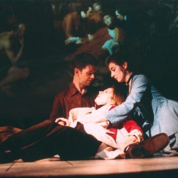 Patrick Conner and Tracey Ferencz holding Brenda Bazinet. All are on the floor, with period costumes on.