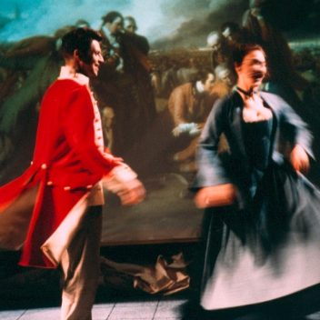 "Patrick Conner & Tracey Ferencz wearing clothing from the 1770, in motion with the painting ""The Death of General Wolfe"" behind them"