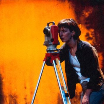 Susan Coyne looking though a machine on a tripod. The background is a burnt yellow