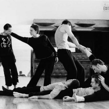 Three people laying on each other on the floor, three people standing, posed. They are in rehearsal and in black and white
