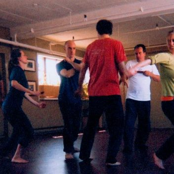 A group of six people in rehearsal, they are all moving and are in a circle