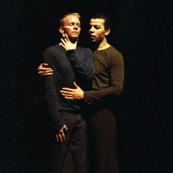 Ray Hogg holding Darryl Tracy from the side. Both are standing, the background is black