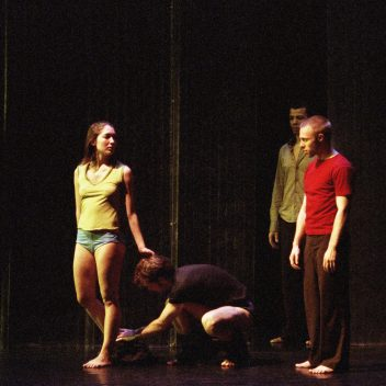 Three people on stage standing, one person kneeling and touching one of their feet