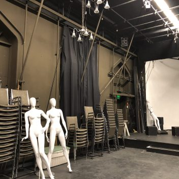 Rehearsal Hall with chairs stacked high and a few mannequins