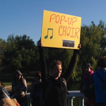 """Group of people outside, one person is holding a sign high which says """"pop-up choir"""""""