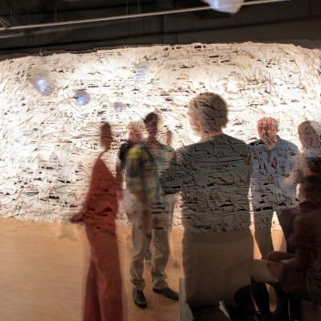 A group of people in a circle, some are seated but the rest are standing. Their bodies are translucent, so a textured wall can be seem