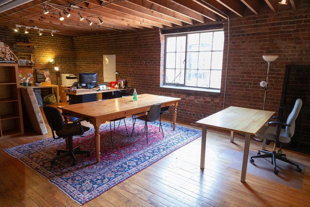 Nightswimming's office with a table in the centre, a desk to the right, and a desk on the far left featuring brick walls and wooden floors.