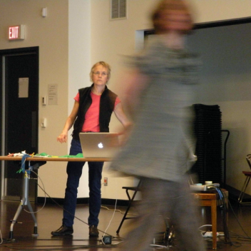 Ellen Moffat behind a table with a laptop, looking at Katherine Ricketts's as they move. They are in a rehearsal hall
