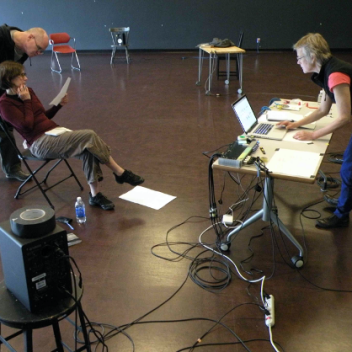 Three people in a rehearsal hall. One is sitting looking at a paper they are holding, one is behind them, also looking at that paper. One person is standing behind a table, looking at a laptop