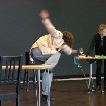 Two people in a rehearsal room, one is in motion the other is not.